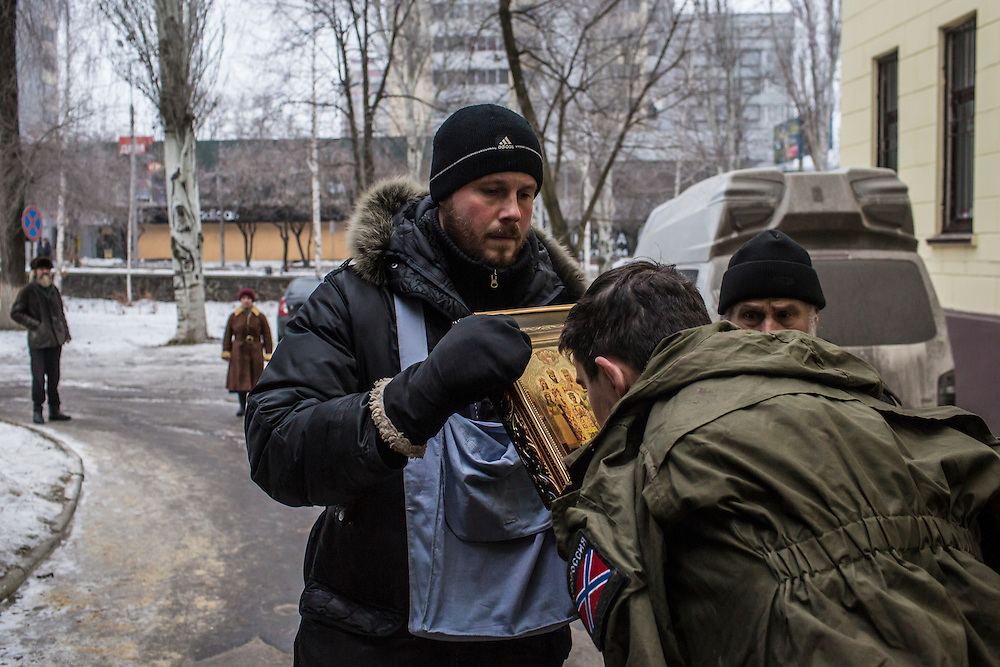 DONETSK, UKRAINE - JANUARY 26, 2015: A wounded rebel fighter kisses an Orthodox religious icon outside Vishnevskogo Hospital in Donetsk, Ukraine. Heavy fighting in recent days has killed dozens of people. CREDIT: Brendan Hoffman for The New York Times