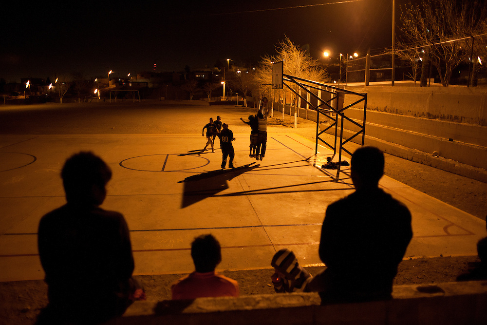 """Youth, primarily of the gang """"Los Noveno"""" hang out and watch a basketball game."""