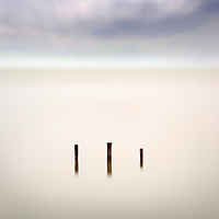 Three wooden poles, probably the remains of an old wharf, emerging from the still waters of  Etang de Vaccarés, the largest lake in Camargue, France. Taken on a rainy evening of mid April.  The ethereal effect comes from a very long exposure - about 4 minutes - combined with the rain: the long exposure has made the water perfectly smooth and blurred the clouds in the sky, whilst the rain provided a sort of natural flou filter to the entire image.
