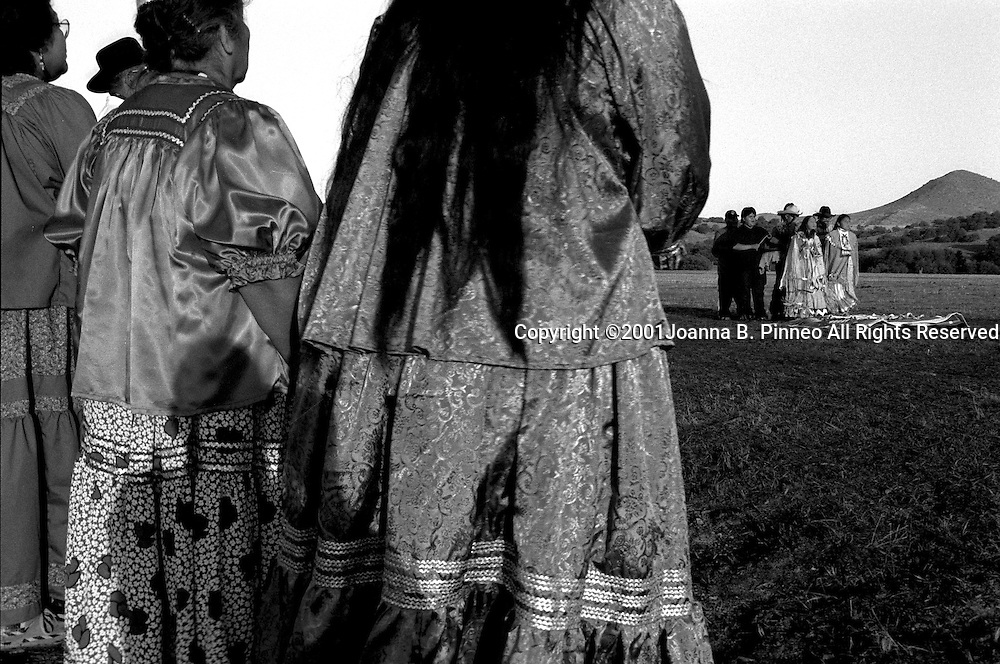 """""""Na ii ees"""",  The Apache Woman's Puberty Ceremony   (or  Sunrise Dance) Many Apache girls today have a puberty ceremony preparing her for womanhood. """"Na ii ees""""  is a ritual enactment of the Apache origin myth known as  """"Changing Woman"""".  Changing Woman's power grants longevity. The power is transferred to the pubescent girl through songs sung by the medicine man.   Tara and a companion start early in the morning and the girls must dance 36 songs each of two mornings while the medicine men drum. Family and community members stand in a semi circle in support during the ceremony  From the collection of Grrlstories (www.grrlstories.org) a project that explores the ways girls come of age in America."""