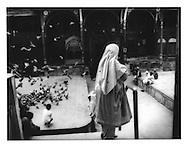 Kashmiri woman surveys activity in courtyard of Shah Hamden Mosque, Srinagar, Indian Administered Kashmir.