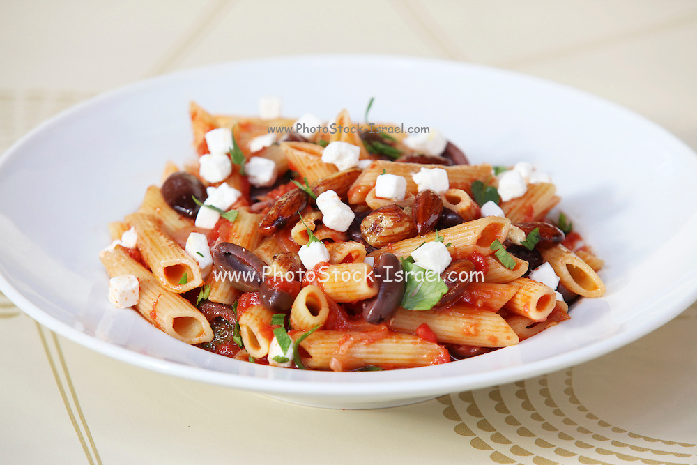 A serving of vegetarian Penne pasta with olives, almonds and vegetables