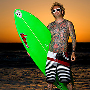 Tattoo artist Mark Longenecker poses with his surfboard on the Gulfcoast of near St. Petersburg, Florida May 13, 2008. Photo by Scott Audette