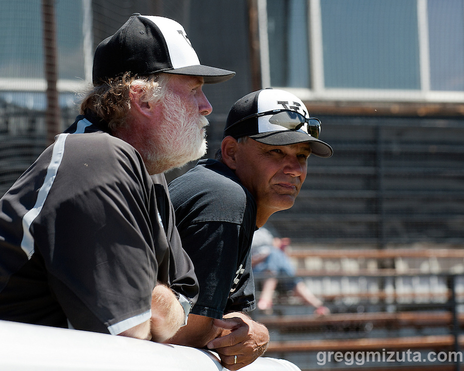 Vale coaches Rick Bates and Rick Yraguen watch the team warmup before the start of the Vale-Nyssa doubleheader at Vale High School, Vale, Oregon, May 8, 2015.