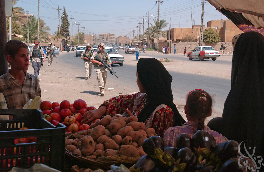 An Iraqi mother and her daughters shop for vegetables at a neighborhood produce stand as soldiers with the U.S. Army 4th Infantry Division, 1st Battallion, 12th regiment  pass by on a daylight presence patrol August 24,2003 through Samarra, Iraq.