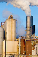 A factory emits smoke and steam on a cold winter day.