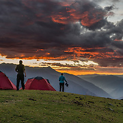 An orange sunset illuminates clouds over the Cordillera Negra at Camp 9 at 4023 meters elevation in the Cordillera Blanca (below Huishkash/Huishcash and well above Hualcayan), Andes Mountains, Peru, South America. This was our last night of trekking 10 days around Alpamayo in Huascaran National Park (UNESCO World Heritage Site).