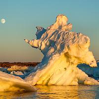 Canada, Manitoba, Churchill, Full moon rises above melting sea ice on Hudson Bay at sunset on summer evening