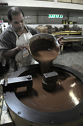 A worker pours chocolate for preparing chocolate Easter eggs before the upcoming Easter at the company of Chocolate Arrufat in Buenos Aires, capital of Argentina, on March 27, 2013. According to local press, the company processed 12,000 kilos of chocolate this season., March 27, 2013. Photo by Imago / i-Images...UK ONLY.