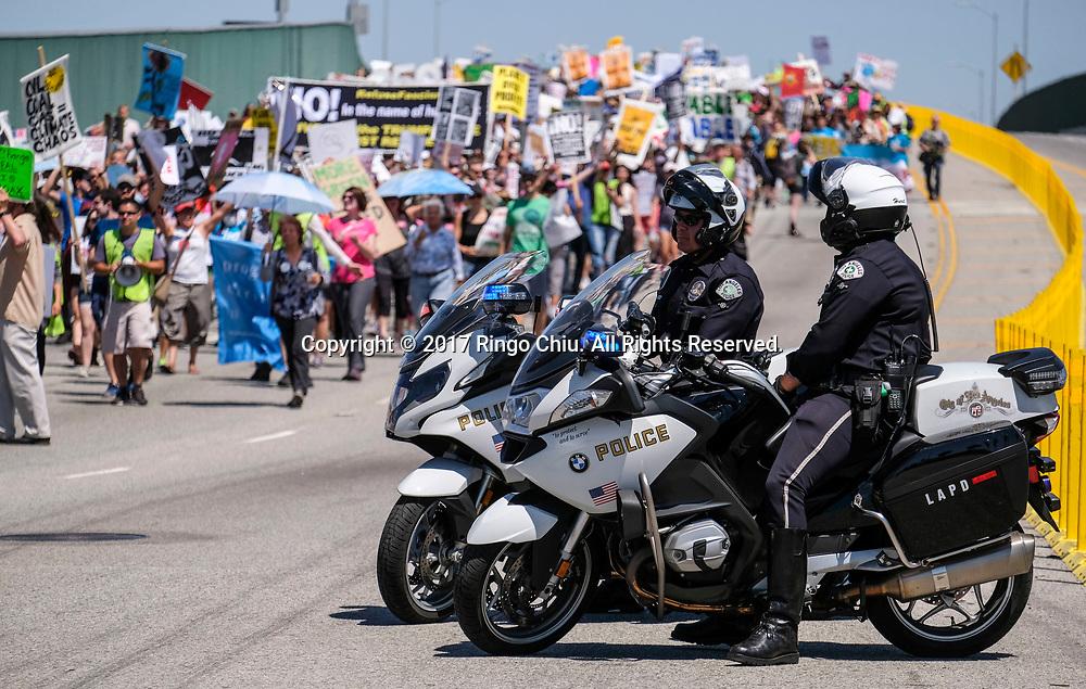 4月29日,美国加利福尼亚州洛杉矶,大批群众参与「人民气候游行」。当天,美国多个城巿有民众趁总统特朗普就任一百日上街游行,反对特朗普对气候变化的态度。新华社发 (赵汉荣摄)<br /> Police officers stand guard in front of a refinery as people participate in a climate change awareness march and rally, in Los Angeles, the United States, Saturday, April 29, 2017. The gathering was among many others of its kind held nationwide marking President Donald Trump's 100th day in office. (Xinhua/Zhao Hanrong)(Photo by Ringo Chiu/PHOTOFORMULA.com)<br /> <br /> Usage Notes: This content is intended for editorial use only. For other uses, additional clearances may be required.