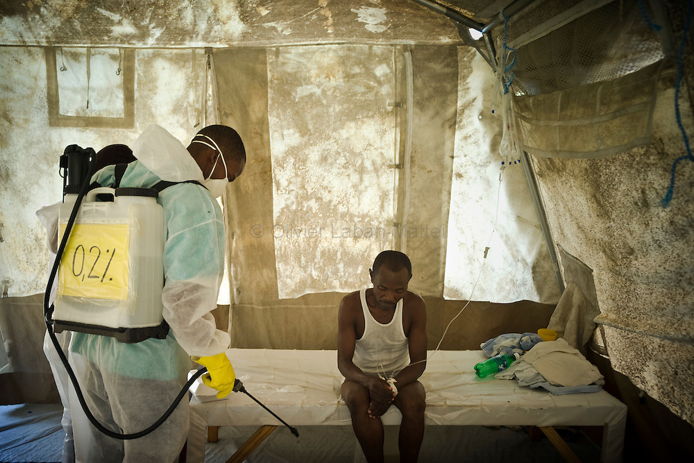 The number of cholera victims in Cité Soleil, a slum of Port-au-Prince, is increasing day by day exponentially, according to a doctor of Doctors Without Borders./// An employee from Doctors Without Borders decontaminates with a chlorine solution a man coming from Cite Soleil and affected by cholera, at the Sarthe hospital in Port-au-Prince.