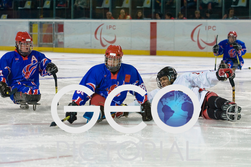 TURIN, ITALY - MARCH 11: #88 Nathan Stephens of Great Britain manoeuvres the puck around a Canadian defender during the opening game of the preliminary round men's sled hockey between Great Britain and Canada; Day 1 Turin 2006 Winter Paralympic Games; Torino Esposizioni; Turin, Italy.