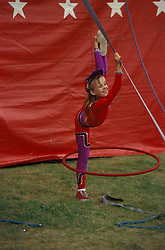 "Circus, young girl performs with hula hoops. Bentley Bros. circus, one of the few remaining ""mud show"" circus performing under a canvas big top."