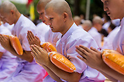 19 JULY 2014 - KHLONG LUANG, PATHUM THANI, THAILAND: Men being ordained as monks pray while they hold their new robes at Wat Phra Dhammakaya. Seventy-seven men from 18 countries were ordained as Buddhist monks and novices at Wat Phra Dhammakaya, a Buddhist temple  north of Bangkok, Saturday. It is the center of the Dhammakaya Movement, a Buddhist sect founded in the 1970s and led by Phra Dhammachayo (Phrathepyanmahamuni). It is the largest temple in Thailand. The Dhammakaya sect has an active outreach program that attracts visitors from around the world.    PHOTO BY JACK KURTZ