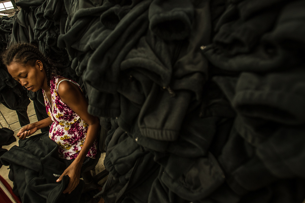 OUANAMINTHE, HAITI - NOVEMBER 7, 2013: A pregnant worker inspects Columbia brand fleece jackets at a garment factory in CODEVI industrial park in Ouanaminthe, Haiti. Low wages and factories like CODEVI in free trade zones have led many private US based companies like Hanes, Calvin Klein, Columbia, Levis and Lucky Brand to hire Haitians to sew their clothes.  CREDIT: Meridith Kohut for The New York Times