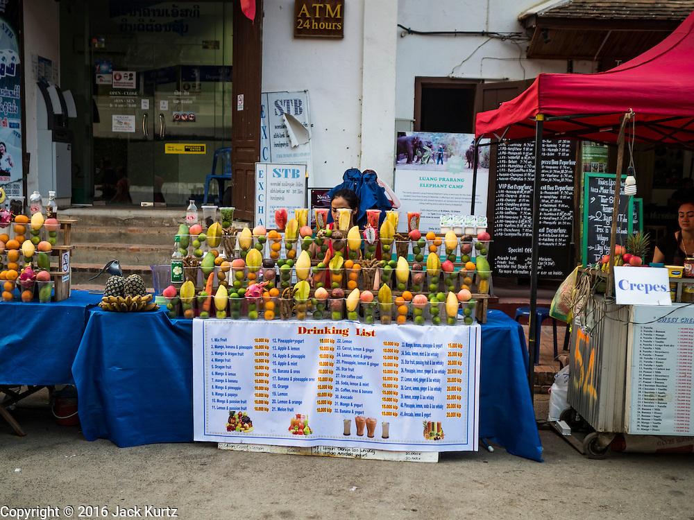 "11 MARCH 2016 - LUANG PRABANG, LAOS:  A fruit smoothie stand on the street of Luang Prabang. Luang Prabang was named a UNESCO World Heritage Site in 1995. The move saved the city's colonial architecture but the explosion of mass tourism has taken a toll on the city's soul. According to one recent study, a small plot of land that sold for $8,000 three years ago now goes for $120,000. Many longtime residents are selling their homes and moving to small developments around the city. The old homes are then converted to guesthouses, restaurants and spas. The city is famous for the morning ""tak bat,"" or monks' morning alms rounds. Every morning hundreds of Buddhist monks come out before dawn and walk in a silent procession through the city accepting alms from residents. Now, most of the people presenting alms to the monks are tourists, since so many Lao people have moved outside of the city center. About 50,000 people are thought to live in the Luang Prabang area, the city received more than 530,000 tourists in 2014.      PHOTO BY JACK KURTZ"