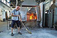 Murano island. Formia glass factory, maintenance workers inspect the furnaces at late afternoon.