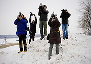 Photographers use a snow bank to gain height as they photograph Republican presidential hopeful Mike Huckabee, as he goes running at Grays Lake in Des Moines, Iowa, Monday, December 31, 2007.