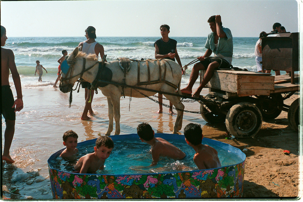Palestinian chldren bathe in a kiddie pool next to a donkey cart on the sands of the Mediterranean coast of Gaza City in the Gaza Strip Friday July 27, 2001. Despite the 11 months of violence Israelis and Palestinians take a break to enjoy the Mediterranean beaches and the Dead Sea, where under growing tensions and in the case of Gaza under closure people try to  make the best of their summer and carry on a normal life.