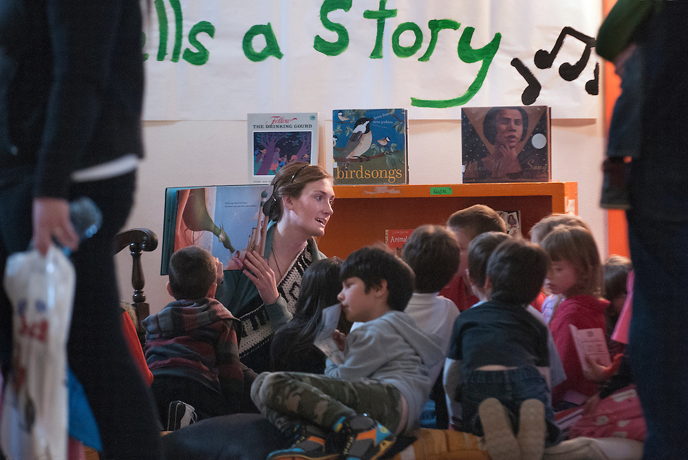 """em040314j/a1/Katherine Keener, the music teacher at Atalaya Elemtary, sings a story to a group kids. The PTA and teachers at Atalaya Elementary School held a Story Jam in the gym of their temporary location at the Kaune building in Santa Fe Thursday evening. Students were treated to several stories told by people ranging from professional story tellers and authors to teachers and parents. Atalaya Elementary is a Title 1 school with at least 40% of the kids recieving free lunch or are considered """"disadvantaged"""". Story Jam not only offered kids a chance to hear some stories but also book making, crafts and books to take home. And parents got an opportunity to attend classes to help their young students improve their literacy skills. This was the first Story Jam but the school hopes to make it an annual event. Eddie Moore/Albuquerque Journal"""