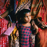 Holding on, a child visits a Bangladeshi clinic with her pregnant monther, who will be given a checkup and told to space her children.