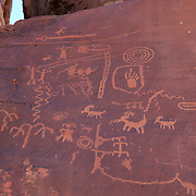 Ancient Anasazi petroglyphs cover a rock face, known as Atlatl Rock in the Valley of Fire State Park, Nevada. The rock art may be more than 1,500 years old. The rock is named for the two symbols at the top, immediately below the bighorn sheep. The object below the sheep is the atlatl and the object just below that is the dart. An atlatl is a hunting device that is also sometimes called a spear thrower.
