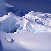 Extreme snowboarder Tom Burt glides among the crevasses of the Ruth Glacier near Mount McKinley, Denali National Park, Alaska