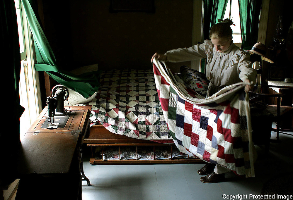 """mother - des moines, may 8 -- What would a mother be doing on a Sunday in 1900?  """"Working"""", said Living History Farms employee Shannon Bardoe, who greets visitors at the 1900 farm and reenacts life during that time period.  Bardoe was busy this day with household chores like washing dishes, and here folds a quilt that she has been working on for four years.  """"There might have some time for relaxation,"""" said Bardoe, who has worked at the farm since 2000.  photo by david peterson  miDes Moines, Ia."""