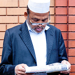 London, UK - 20 July 2012: a man reads a newspaper in front of the East London Mosque right after the prayer that celebrates the first day of Ramadan.