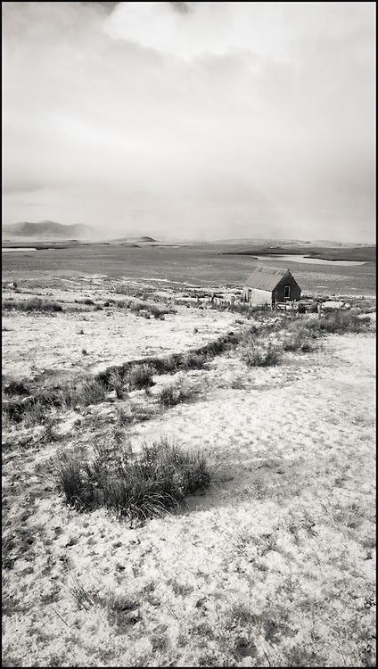 Corrugated Metal Hut in field on Isle Of Lewis, Scotland. Snow covering ground. Storm clouds over hills in distance.