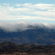 The clouds rolling over the mountains just after a winter storm dropped snow atop the peaks by Lake Havasu City, Arizona.