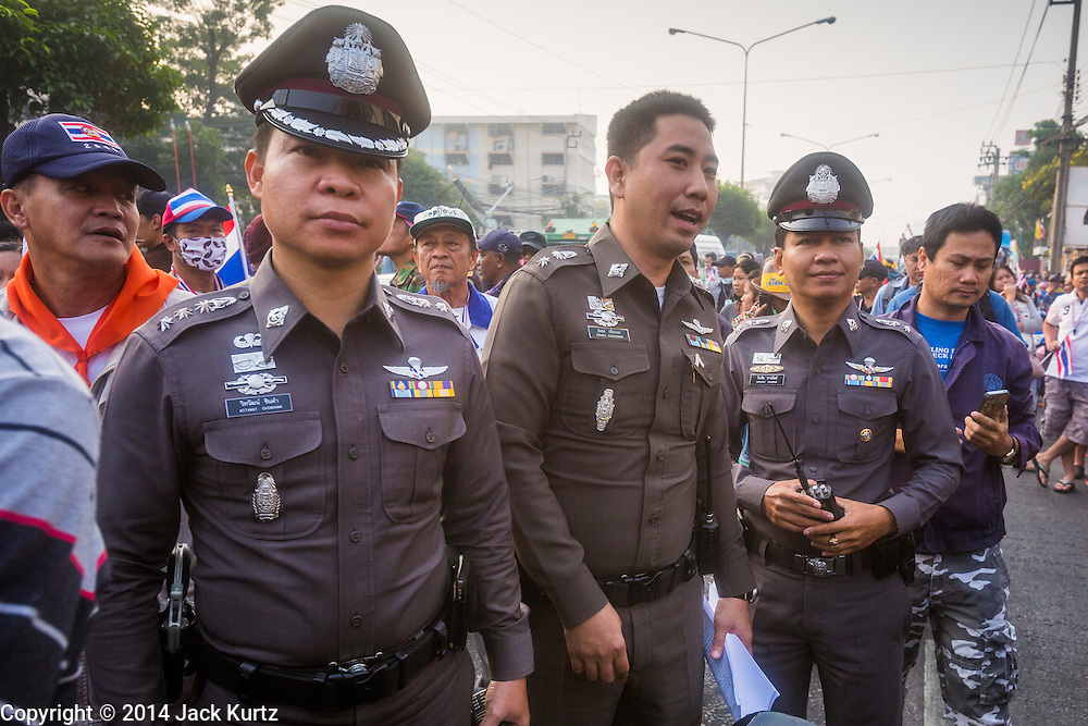 26 JANUARY 2014 - BANGKOK, THAILAND: Thai police watch anti-government protestors shut down the polling place at Bang Kapi School. Anti-government protestors forced the closure of polling places in Bangkok Sunday as a part of Shutdown Bangkok. Early voting was supposed to be Sunday January 26 but blocked polling places left hundreds of thousands of people unable to vote casting the February 2 general election into doubt and further gridlocking Thai politics. Protestors blocked access to gates and entry ways to polling places and election officials chose the close them rather than confront protestors. Shutdown Bangkok has been going for 12 days with no resolution in sight. Suthep, the leader of the anti-government protests and the People's Democratic Reform Committee (PDRC), the umbrella organization of the protests,  is still demanding the caretaker government of Prime Minister Yingluck Shinawatra resign, the PM says she won't resign and intends to go ahead with the election.    PHOTO BY JACK KURTZ