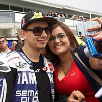 Yamaha Factory rider Jorge Lorenzo poses with a fan before the U.S. MotoGP race at Mazda Raceway Laguna Seca, Sunday, July 29, 2012.