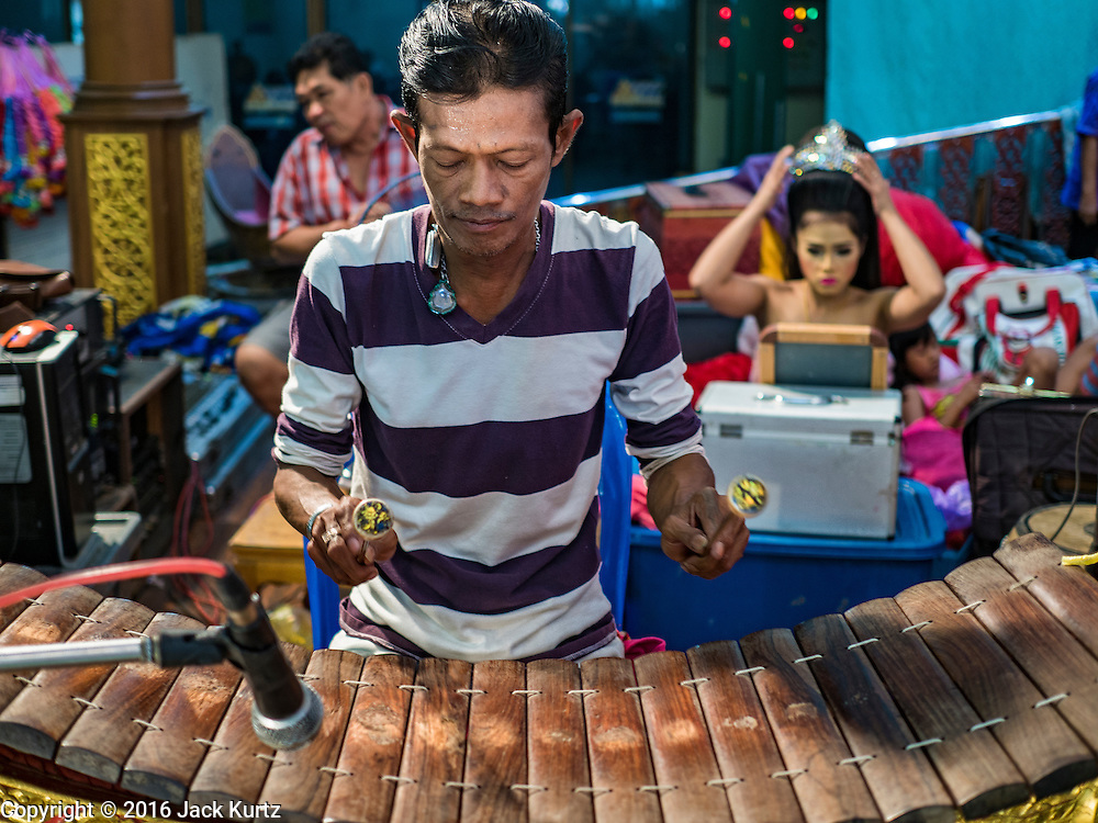 "30 JANUARY 2016 - NONTHABURI, NONTHABURI, THAILAND:  A musician performs while other members of the cast put on their makeup during a ""likay"" show at Wat Bua Khwan in Nonthaburi, north of Bangkok. Likay is a form of popular folk theatre that includes exposition, singing and dancing in Thailand. It uses a combination of extravagant costumes and minimally equipped stages. Intentionally vague storylines means performances rely on actors' skills of improvisation. Like better the known Chinese Opera, which it resembles, Likay is performed mostly at temple fairs and privately sponsored events, especially in rural areas. Likay operas are televised and there is a market for bootleg likay videos and live performance of likay is becoming more rare.    PHOTO BY JACK KURTZ"