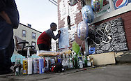 Mackenzie Arias (9) signs a memorial poster for Levy King Flores  outside a bodega at the intersection of First Street and Carpenter Avenue in the City of Newburgh, NY on Saturday, January 16, 2010. Flores (17) was stabbed by an unnamed 13 year-old on Wednesday at the scene and later died en route by helicopter to Westchester County Medical Center that evening.