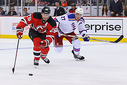 Oct 21, 2014; Newark, NJ, USA; New Jersey Devils left wing Patrik Elias (26) skates with the puck while being pursued by New York Rangers defenseman Ryan McDonagh (27) during the second period at Prudential Center.