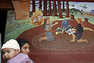 A mural portraying the brutality inflicted on the Maya polulation by the government during the 80's provides a backdrop for a mother and her daughter walking to the market.