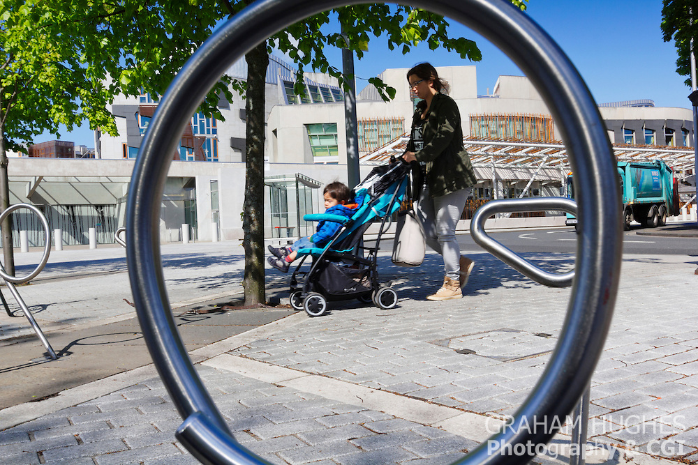 Scottish Parliament Building. Mother With Child In Pram through circle of bike rack.