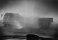 Heavy truck traffic through an industrial zone throws up clouds of blinding dust on National Hwy 110 in Ningxia Province, China.