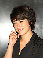 Hispanic woman (20-30) smiling while listening to a mobile phone.
