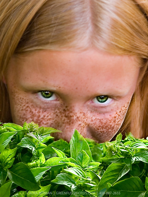A young woman with red hair, bright green eyes and freckles gazes up directly at the viewer while holding a bunch of genovese basil in front of her face.