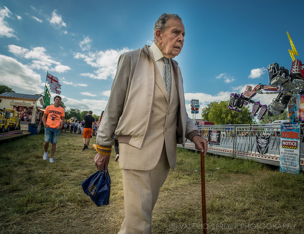"""""""I have seen many..."""" an old man walks through the fun rides"""