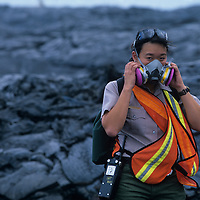 USA, Hawaii, Volcanoes National Park,  Female park ranger wears respirator against fumes from Kilauea volcano eruption