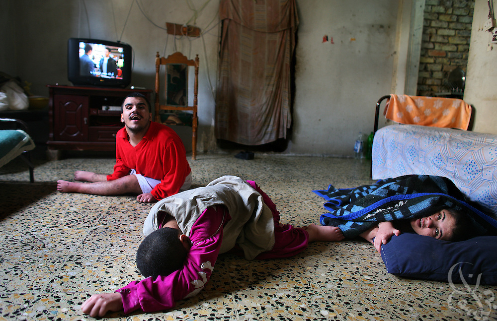Hooda (right), 27, Maha (center), 17, and Yusef Dawood (left), 16, are mentally handicapped Iraqis who live with their father Sa'adoon, mother and 3 other siblings in a homeless community at the former Air Force headquarters in Baghdad, Iraq on Sunday, Oct. 22, 2006. Hundreds of Iraqi families who cannot afford elevated post war housing costs have taken up residence in the abandoned air force base, making do with what they can.