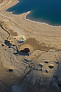 An aerial view showing sink holes along the receding shore line of the Dead Sea in the area of En Gedi .The holes form when a subterranean salt layer that once bordered the sea is dissolved by underground fresh water that follows the receding Dead Sea waters. The sink holes are also found along the Jordanian side of the Dead Sea as well. .The Dead Sea ,the lowest place on the planet ,more than 1300 feet below sea level, is now facing a threat of disappearing : The Dead Sea is Dying..Since the 1950's the Dead Sea has been  dropping in water level at  an alarming rate  not by climatic changes as much as human consumption in the area. The fresh water source from the Jordan and Yarmouk river  that were so detrimental to its survival  have been diverted for irrigation . Industries that extract  Potash ,salt and magnesium on both sides of the Israeli and Jordanian side today have higher pumping costs. .One idea to save the Dead Sea ,called the Red-Dead is being studied by The World Bank ,a proposal to dig a canal from the Red Sea, more than 100 miles south, to replenish the Dead Sea's waters. But with costs estimated at up to $15 billion, there's little optimism it will happen . Environmentalists are  warning  that without a solution  and  as the sea continues to drop in level by one meter per year, this ancient body of water could disappear as it is expected to shrink to lose another third of its area over the next century.(Photo by Heidi Levine/Sipa Press)..