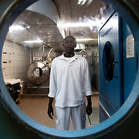 """Ali a sudanese refugee is posing for a portrait as he works in the laundry of the Royal Beach Hotel on February 28 2011. The municipality hung 1,500 red flags around the city as a sign of warning and put up hundreds of banners reading: """"Protecting our home, the residents of Eilat are drawing the line on infiltration."""" Eilat Mayor Meir Yitzhak Halevi said that 10 percent of the city's population was currently made up of migrants and that the residents feel that the city has been conquered...Photo by Olivier Fitoussi."""