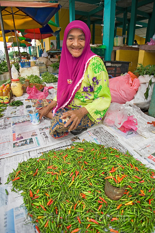 An old Malaysian woman selling chilis and vegetables at a market in Malaysia..