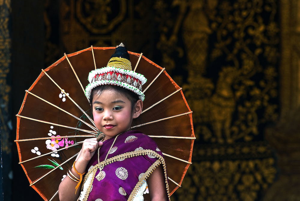 A girl participating in the Lao New Year, (Pi Mai) parade wearing traditional cloathes and makeup.