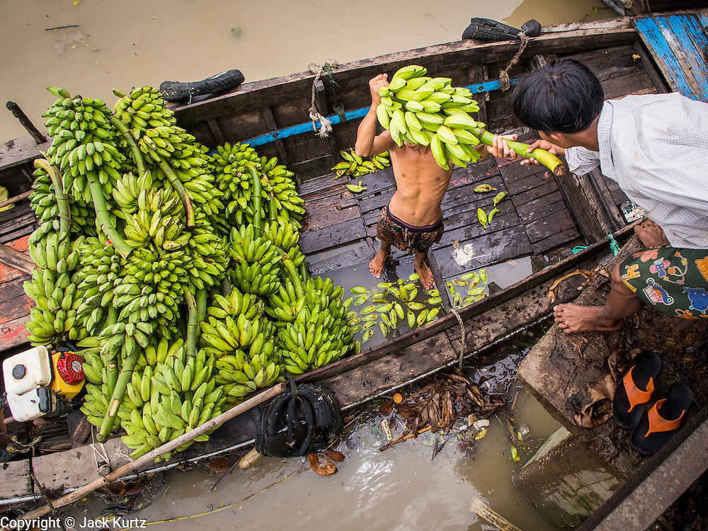 """10 JUNE 2014 - YANGON, MYANMAR:   Porters unload bananas from a river boat at the banana jetty. The """"banana jetty"""" is on the Yangon River north of central Yangon on Strand Road. Bananas, coconuts and other fruit are brought in here from upcountry, sold and reshipped to other parts of Myanmar (Burma). All of the labor here is done by hand. Porters carry the produce to the jetty and porters load the boats before they steam upriver.   PHOTO BY JACK KURTZ"""
