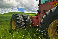 A tractor sits admits tall grass in the Palouse area, Washington. Canon 1Ds, June 2004